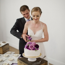 Paper Heart Photography captures bride and groom cutting their cake from Amelie's French Bakery at their spring wedding