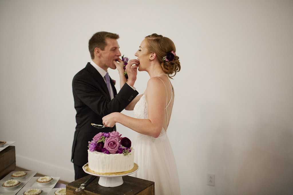 Bride and groom share cake from Amelie's French Bakery during their wedding reception at Foundations for the Carolinas