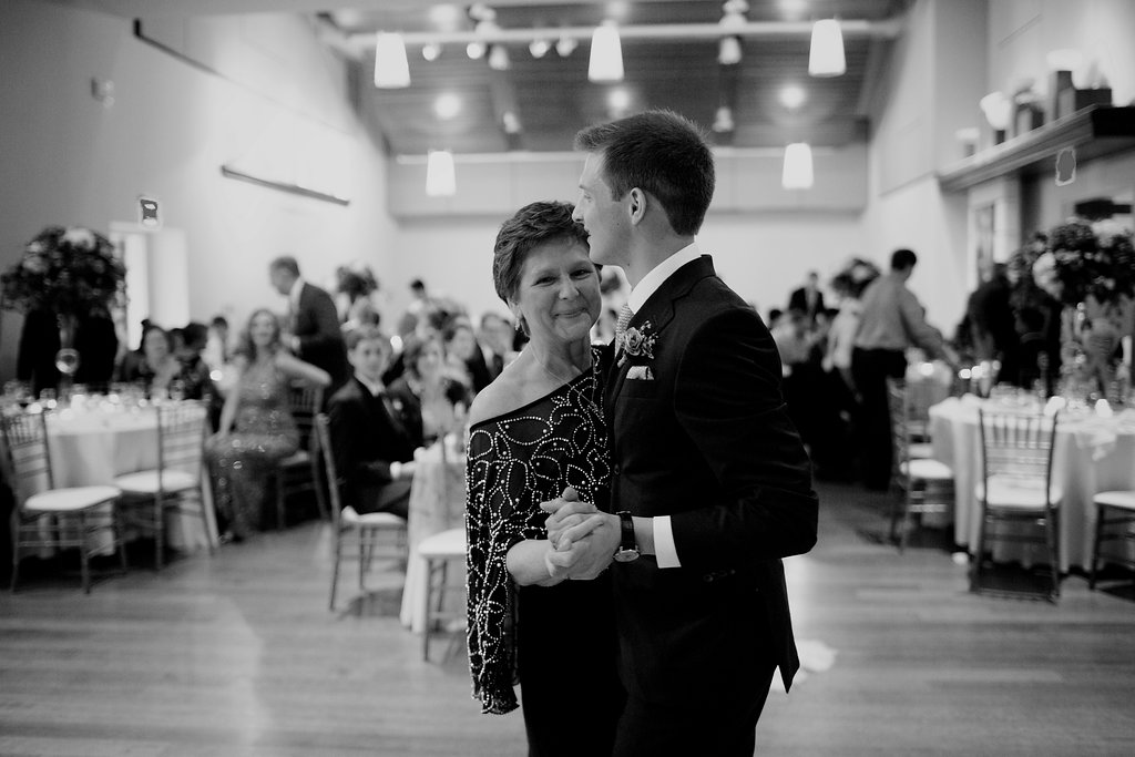 Groom dances with his mother during his Uptown Charlotte wedding coordinated by Magnificent Moments Weddings