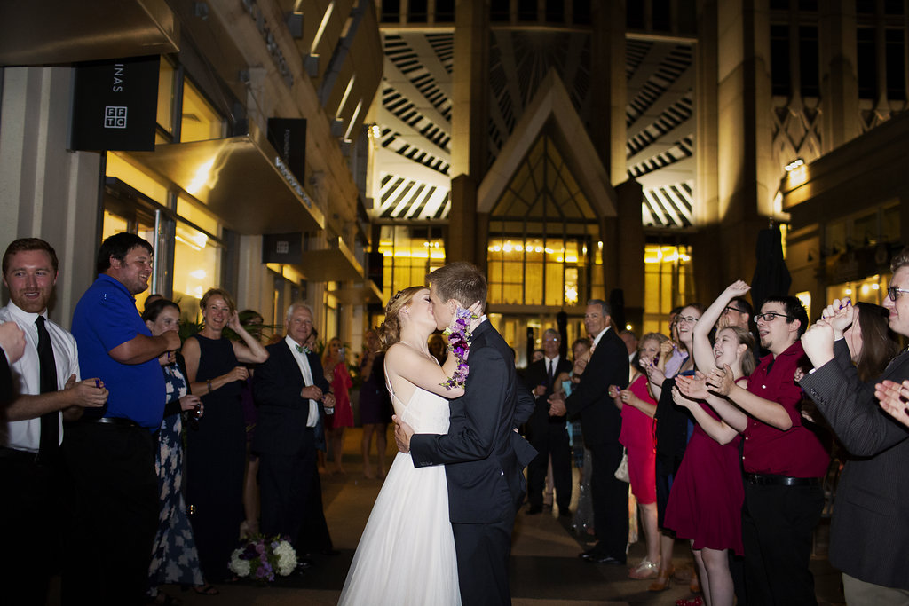Bride and groom share a kiss during their grande exit coordinated by Magnificent Moments Weddings