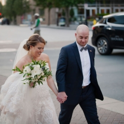 Bride and groom walk hand in hand among the streets of Uptown Charlotte during their summer wedding coordinated by Magnificent Moments Weddings