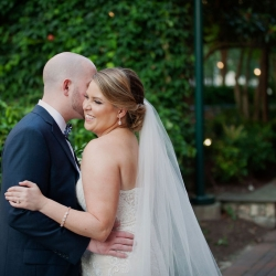 Bride and groom smile at The Green in Uptown Charlotte a perfect place for stunning bridal pictures