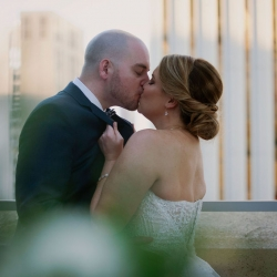 Bride and groom share a kiss captured by Paper Heart Photography on the Terrace of The Mint Museum Uptown