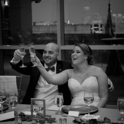 Bride and groom raise a toast to their family and friends before enjoying great food from Something Classic Catering during their wedding at The Mint Museum Uptown