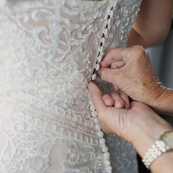 Brides mother buttons the last few buttons on her stunning lace gown as the prepare for their summer wedding at The Mint Museum Uptown