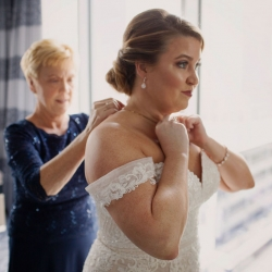 Bride's mother helps finish her look by putting on her wedding jewelry all captured by Paper Heart Photography
