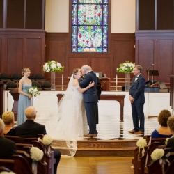 Bride and groom kiss to become husband and wife during their wedding in Uptown Charlotte