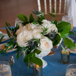 Stunning centerpieces created by Magnificent Moments Wedding Florals featured soft white flowers and navy accents