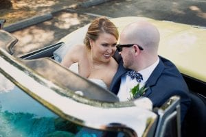 Bride and groom take a drive in a vintage car during their Uptown Charlotte Wedding