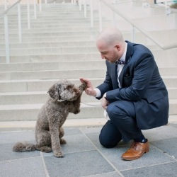 Groom high fives his sweet dog before his summer wedding at The Mint Museum Uptown