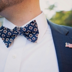Floral bowtie and american flag pins are the perfect accessories for a summer groom marrying at The Mint Museum Uptown
