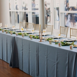 A long head table was the perfect setting for a bride and groom during their wedding reception coordinated by Magnificent Moments Weddings