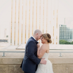 Bride and groom pose among the Charlotte skyline during their summer wedding captured by Paper Heart Photography