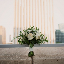 Paper Heart Photography captures a brides stunning bouquet filled with white roses and accents of green created by Magnificent Moments Weddings Florals