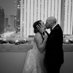 Bride and groom share a kiss among the lights of Uptown Charlotte during their wedding at The Mint Museum Uptown