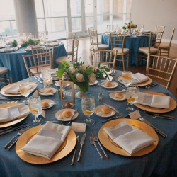 Dusty blue linens and gold chargers are the perfect accents to a summer wedding at the Mint Museum Uptown