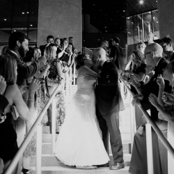 Bride and groom share one last kiss as they leave the Mint Museum Uptown and their wedding reception coordinated by Magnificent Moments Weddings