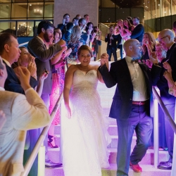 Bride and groom exit their wedding reception a The Mint Museum Uptown through a bubble send off coordinated by Magnificent Moments Weddings