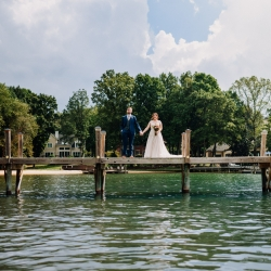 Bride and groom pose atop a dock on Lake Norman during their fall wedding coordinated by Magnificent Moments Weddings
