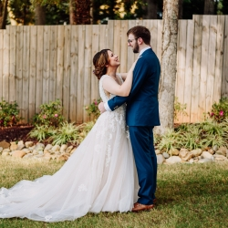 Bride and groom share a sweet look as they prepare to walk down the aisle during their lake wedding just outside of Charlotte, NC