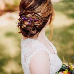 Brides sweet updo has delicate purple flowers during her fall lake wedding
