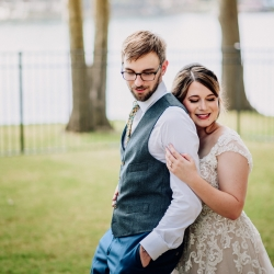 Bride and groom smile as they prepare to exchange vows on stunning Lake Norman