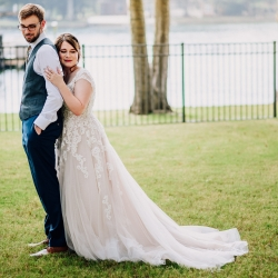 Bride and groom embrace during their lake wedding coordinated by Magnificent Moments Weddings