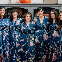 Bride poses with her bridesmaids in matching robes as they prepare for a fall wedding on Lake Norman