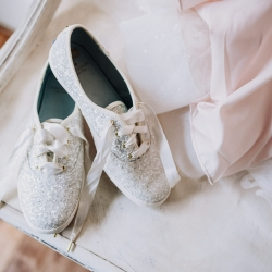 Sparkle sneakers serve as the brides shoes for her lake wedding coordinated by Magnificent Moments Weddings