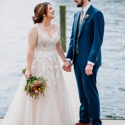 Bride and groom embrace during a fall wedding on Lake Norman captured by Rob + Kristen Photography