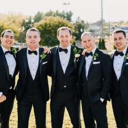 Groom and groomsmen sport black tuxedos from The Black Tux and wear simple white boutonnieres created by Magnificent Moments Weddings