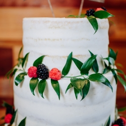 Simple white three tier cake with greenery accents created by Honey Butter Bakery features fun unique topper showing of the home states of the bride and groom