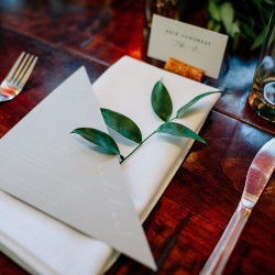 Simple table setting that features white linen napkins, gray modern menu cards, and a single greenery branch create a modern feeling for a fall wedding at Vivace coordinated by Magnificent Moments Weddings