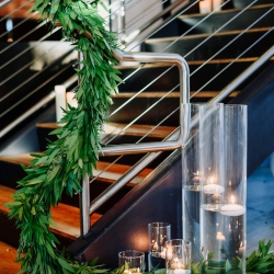 Stunning greenery by Magnificent Moments Weddings are accented by simple glass vases with hurricane candles to create a city chic wedding in Uptown Charlotte