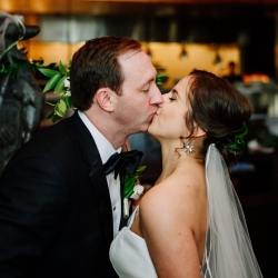 Bride and groom share a kiss during their uptown Charlotte wedding at Vivace coordinated by Magnificent Moments Weddings