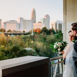 Bride and groom embrace during their fall wedding captured by Rob and Kristen Photography with the stunning Charlotte skyline in the background