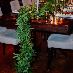 A lush greenery garland created by Magnificent Moments Weddings lines the table at a Vivace reception in Uptown Charlotte