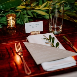 Simple table setting features a white napkin, gray menu card, simple greenery, all for an Uptown Charlotte wedding at Vivace coordinated by Magnificent Moments Weddings