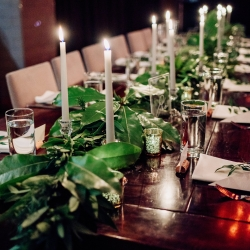 Simple tablescape features tapered white candles surrounded by soft greenery for a wedding at Vivace in Uptown Charlotte
