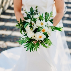 Kristen and Rob Photography capture a detail shot of a simple white and green bridal bouquet created by Magnificent Moments Weddings