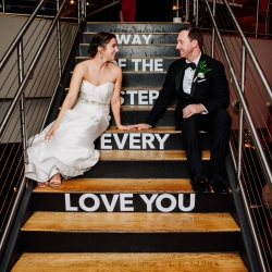 Bride and groom pose on steps at Vivace offering a sentimental message unique to their day