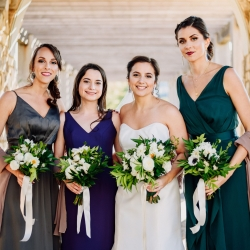Bride poses with her bridesmaids all wearing unique dresses to show of their individuality during a fall wedding at Vivace