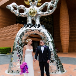 Bride and groom pose among the iconic art of Uptown Charlotte during their fall wedding at The Bechtler