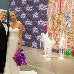 Bride and groom pose among the stunning art of The Bechtler Museum during their fall wedding coordinated by Magnificent Moments Weddings