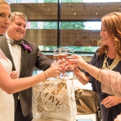 Bride and groom share a toast with guests during their fall wedding at The Bechtler
