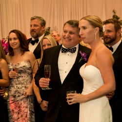 Bride and groom smile as they are toasted by their closest family and friends during their fall wedding captured by Sharon Ashley Photography