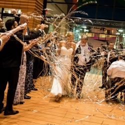 Bride and groom leave through a sea of streamers during their grande exit planned and coordinated by Magnificent Moments Weddings