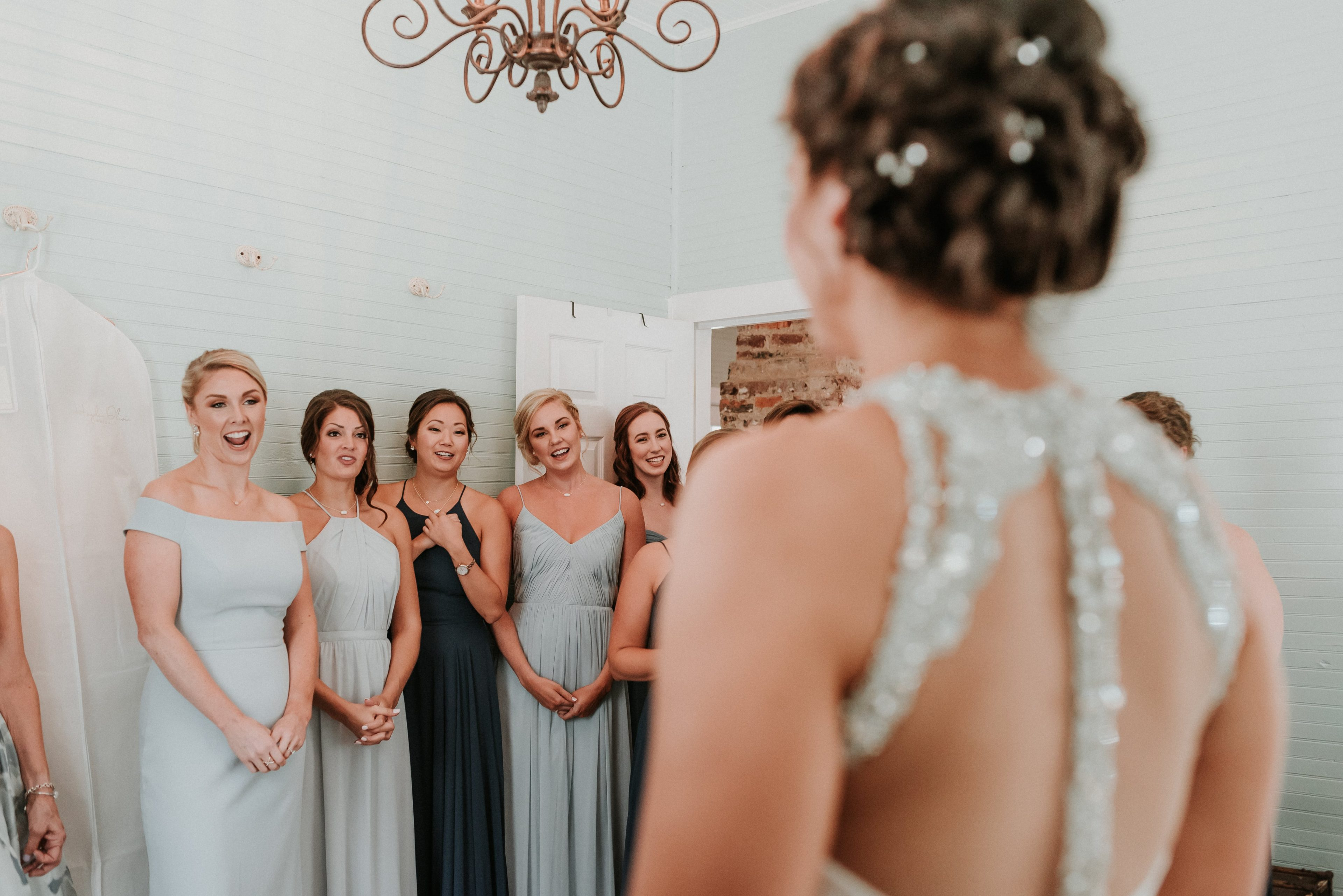 Bridesmaids react to seeing the bride in her Hayden Olivia gown for the first time during her summer wedding at The Ivy Place