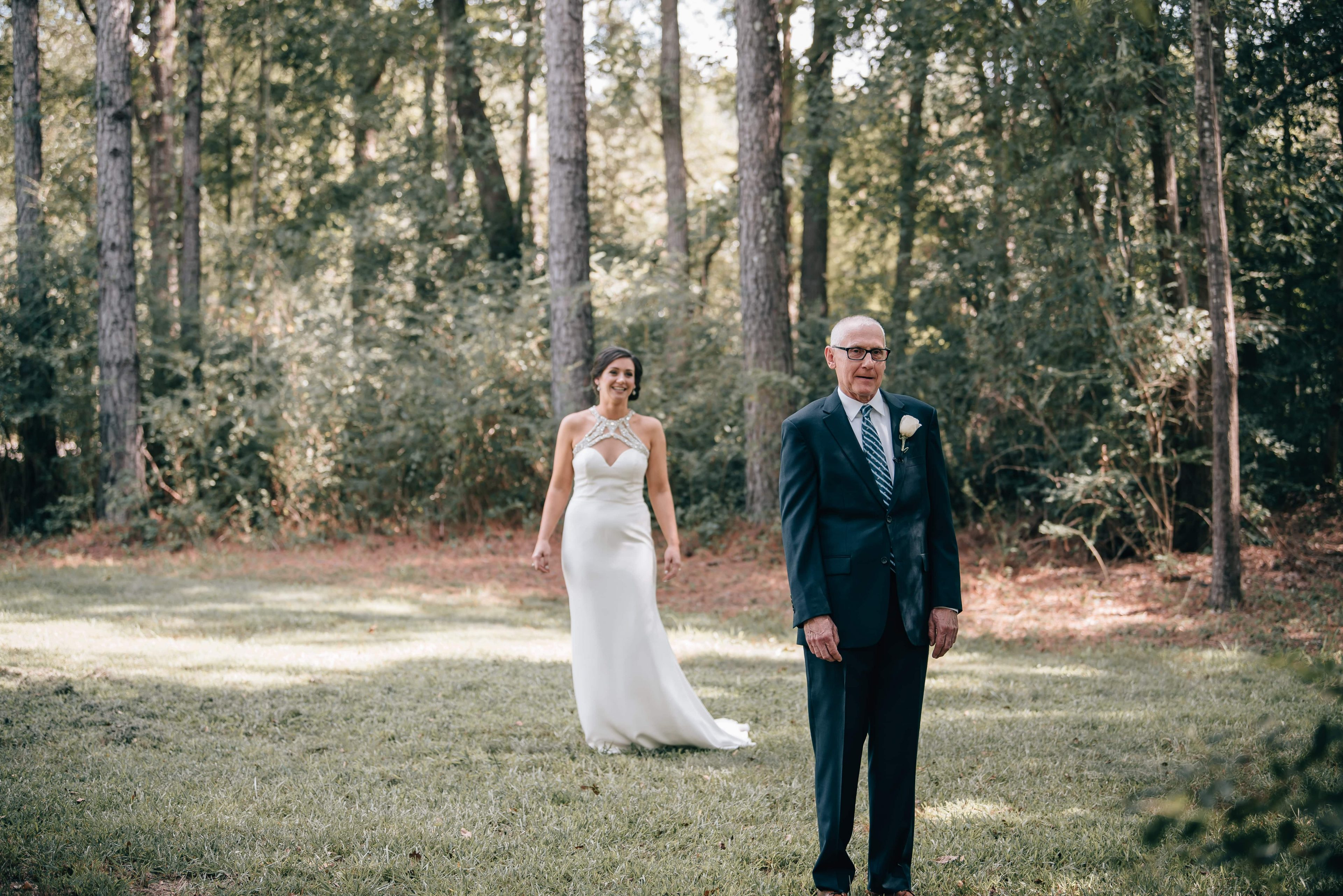 Bride approaches her father for a sweet first look on the grounds of The Ivy Place
