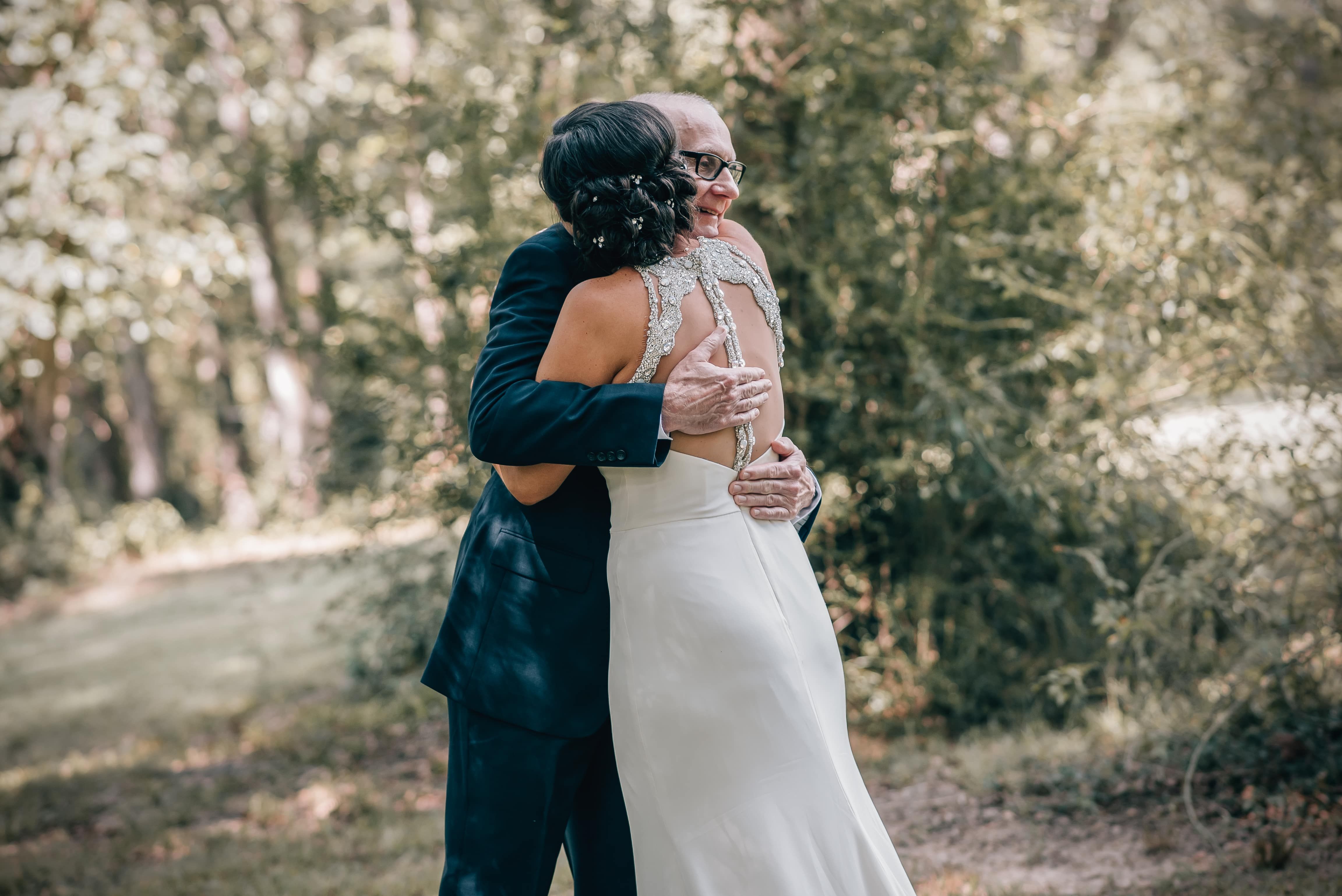Bride and her father embrace after a sweet first look between them captured by Shutter Owl Photography at The Ivy Place